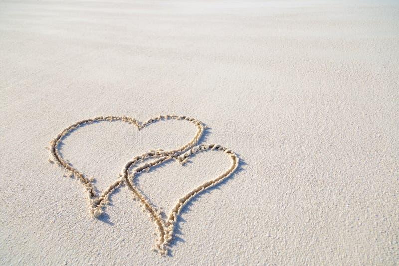 心脏在沙子的形状图画在夫妇的热带海滩,浪漫和蜜月概念背景 免版税库存照片