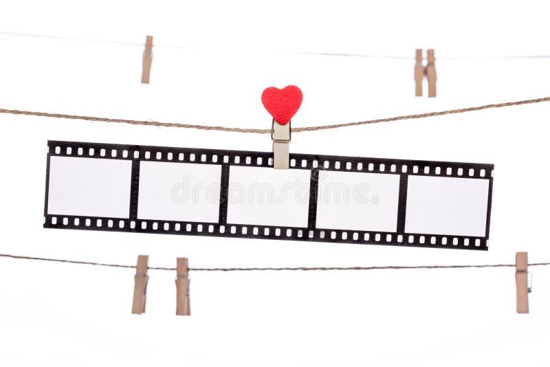 心脏在麻线的形状夹子,垂悬的阴性,爱电影 免版税库存图片