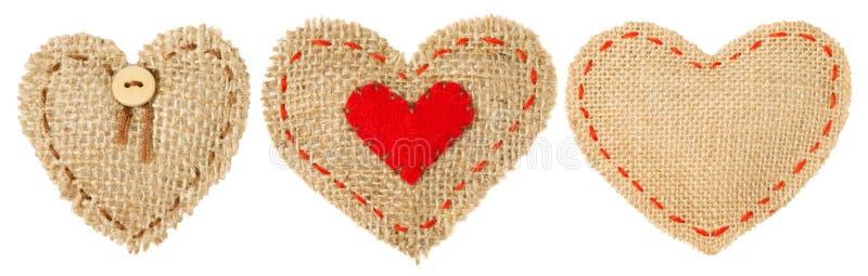 心脏形状与针缝,麻袋布装饰织品,情人节粗麻布的补丁对象 免版税图库摄影