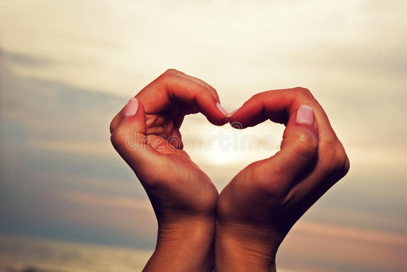 心脏形状在日落的妇女的手上 免版税库存照片