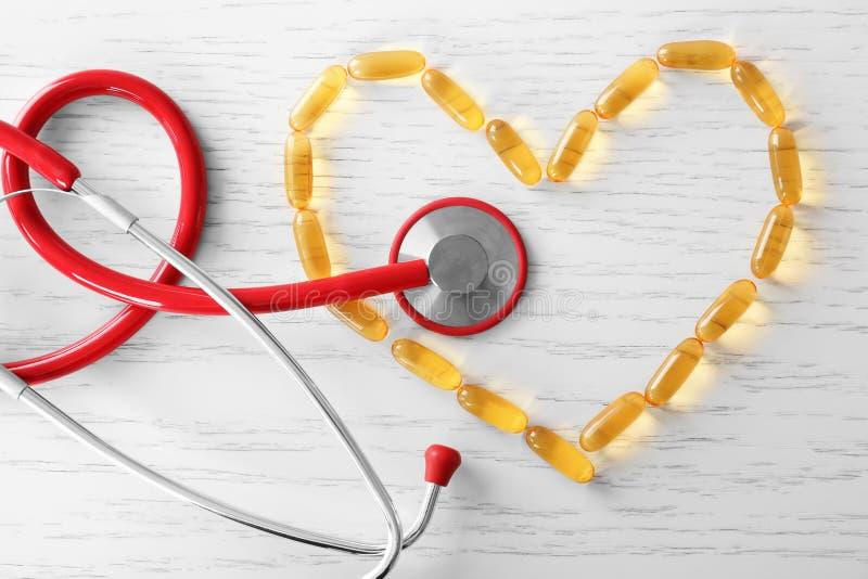 心脏形状由与听诊器的鱼油胶囊做成 免版税库存图片