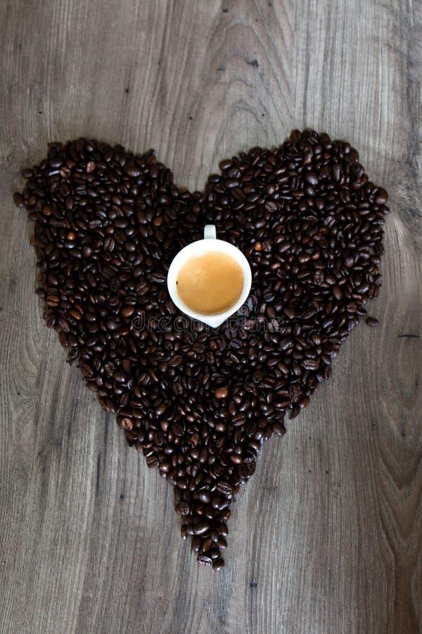 心脏形状由咖啡豆做成在与浓咖啡杯子的一张桌顶部在中部 免版税库存图片
