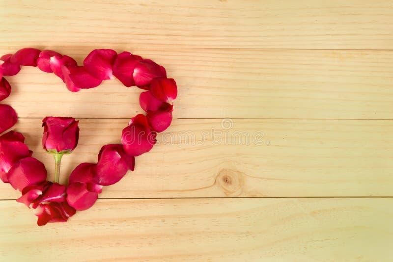 心脏形状由玫瑰花瓣做成在木背景, Valentin 免版税图库摄影