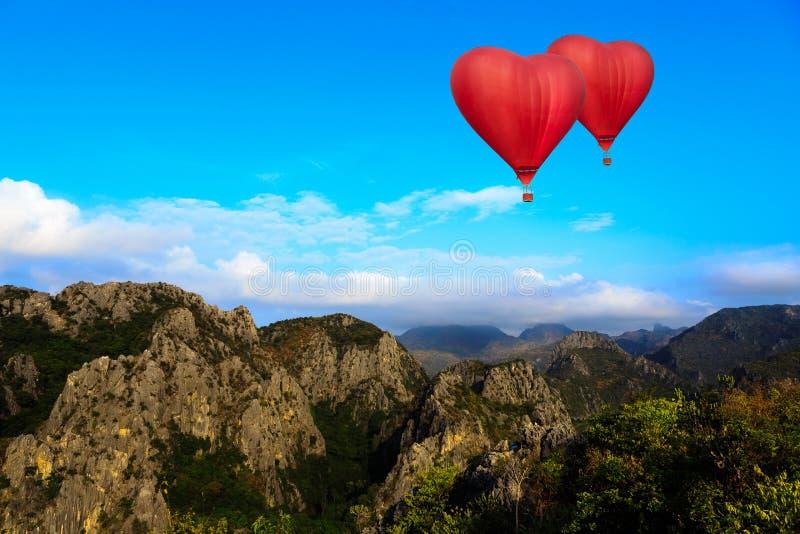 心脏形状迅速增加的飞行在山 图库摄影
