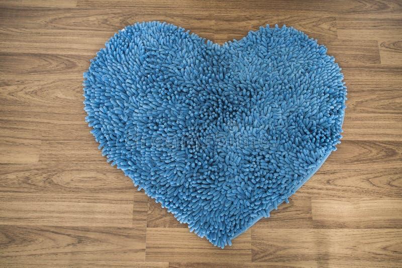 心脏形状,脚在木地板上的刮板地毯 图库摄影