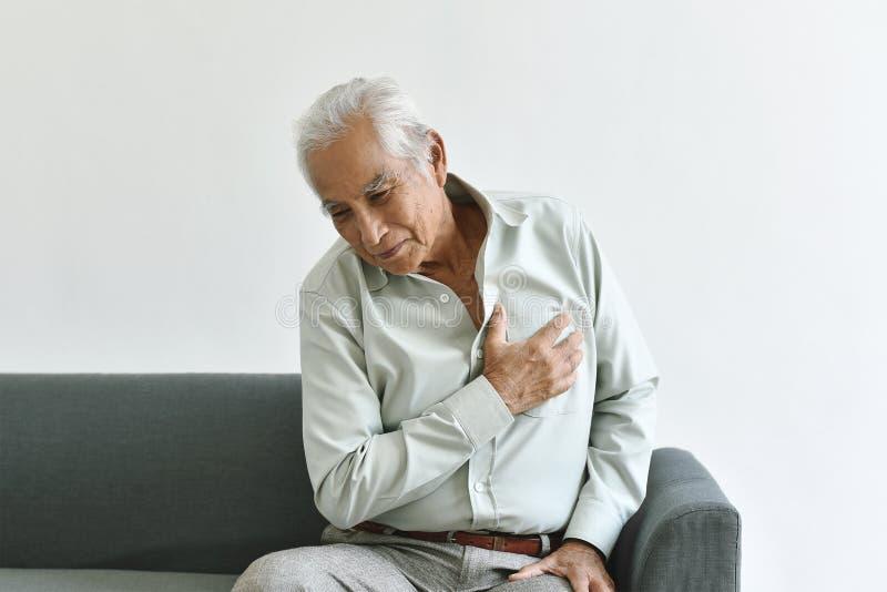 心脏攻击在老人,年长亚裔人的疾病问题用在胸口姿态的手 免版税库存图片