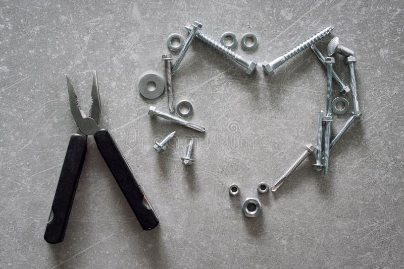 心脏标志由螺丝制成,基本要点 在具体背景的心形的建筑工具 爱滤网符号向量 免版税库存图片