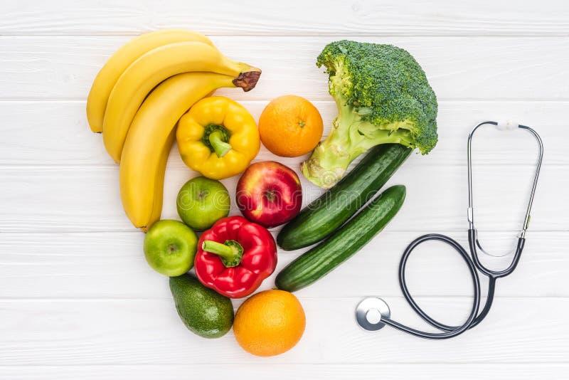 心脏标志顶视图由做了新鲜的水果和蔬菜和听诊器 免版税库存照片