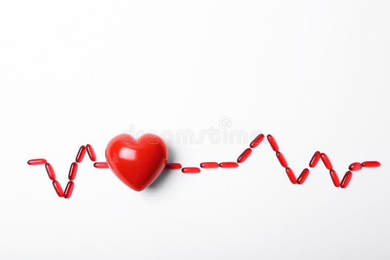 心脏模型和药片在白色背景 心脏病学服务 库存照片