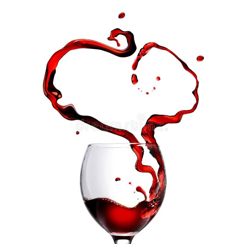 心脏由倒在玻璃的红葡萄酒制成 免版税库存照片