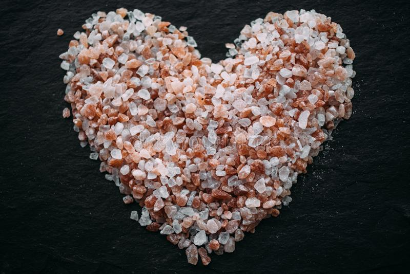 心脏由喜马拉雅盐制成在黑板岩 顶视图 作为背景的心形的盐 免版税库存图片