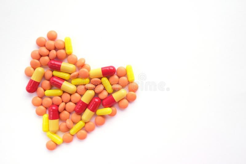 心脏由多色片剂制成在白色背景 o 流行病,止痛药,医疗保健,治疗药片和 免版税库存图片