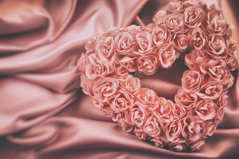 心脏由桃红色玫瑰做成在缎 免版税库存图片