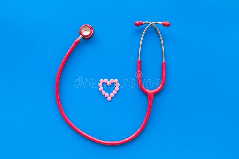 心脏疾患和在蓝色背景顶视图的女性标志诊断和治疗与听诊器的 库存图片