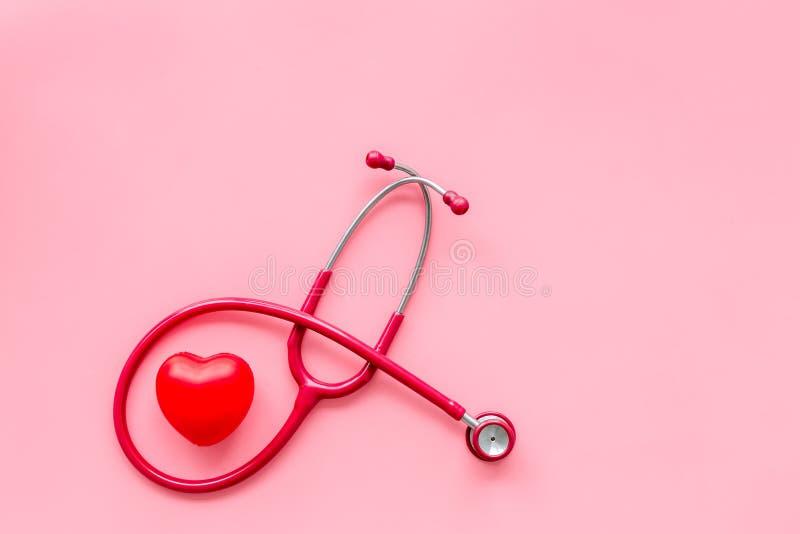 心脏病在桃红色背景顶视图大模型的疾病和心脏诊断和治疗与听诊器的 免版税库存图片