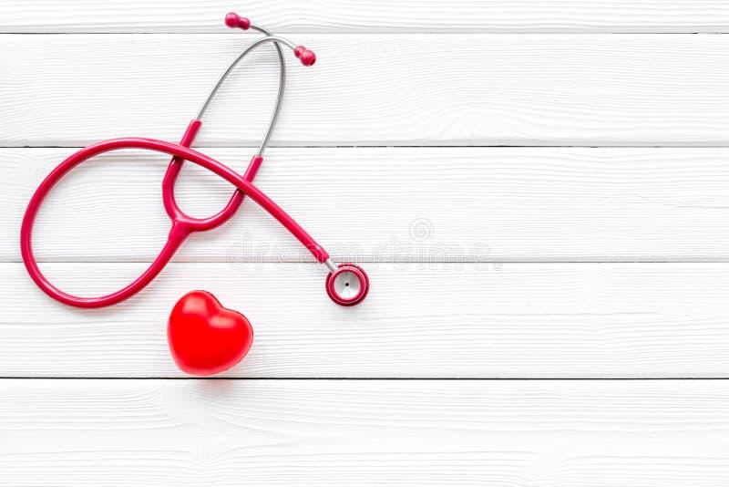 心脏病在白色木背景顶视图大模型的疾病和心脏诊断和治疗与听诊器的 免版税库存照片
