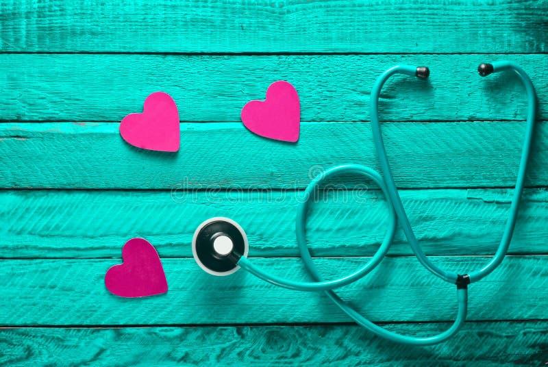 心脏病学设备 重点听您 喜欢的概念心脏 听诊器,绿松石木表面上的心脏 库存照片