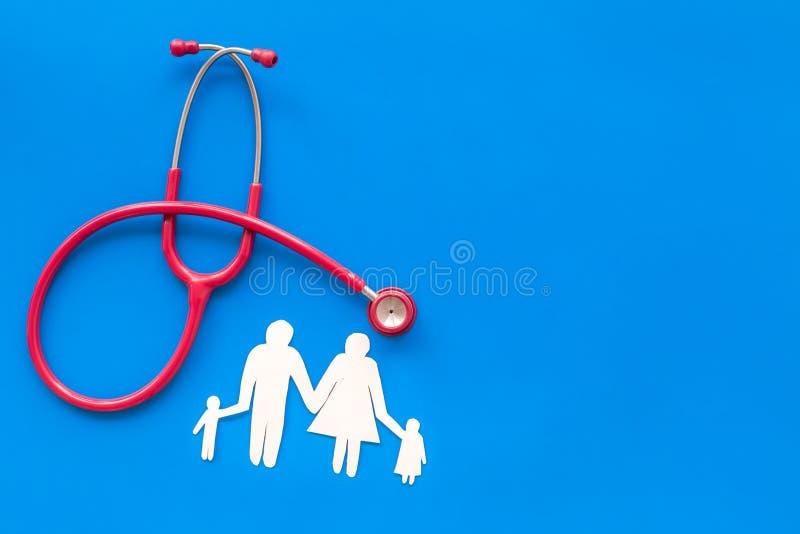 心脏病疾病诊断和治疗与听诊器和家庭纸形象的在蓝色背景顶视图大模型 免版税库存图片