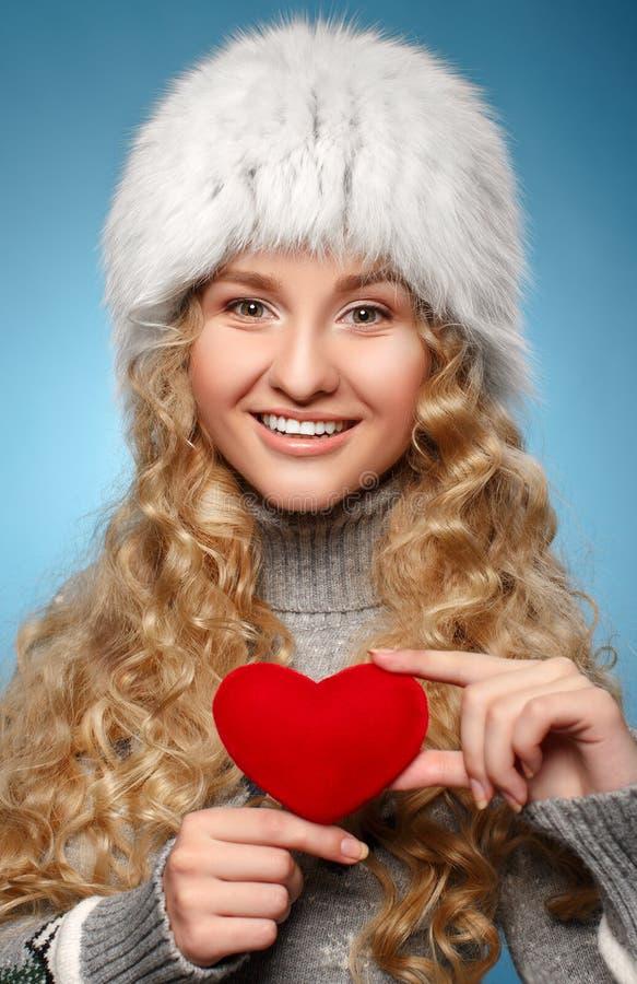 给心脏的冬天衣裳的女孩。情人节的概念 免版税库存照片