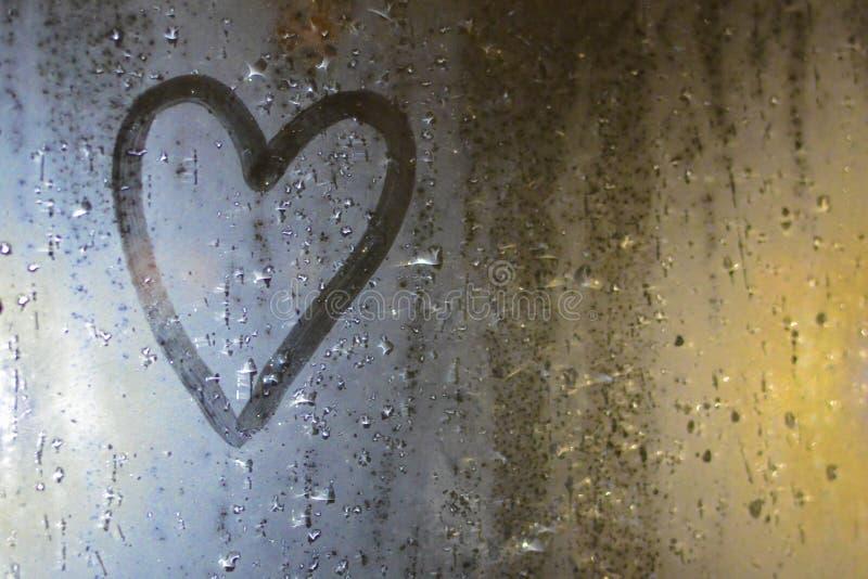 心脏的图象在misted窗口的 概念:哀伤的心情、悲伤和乏味 免版税库存照片