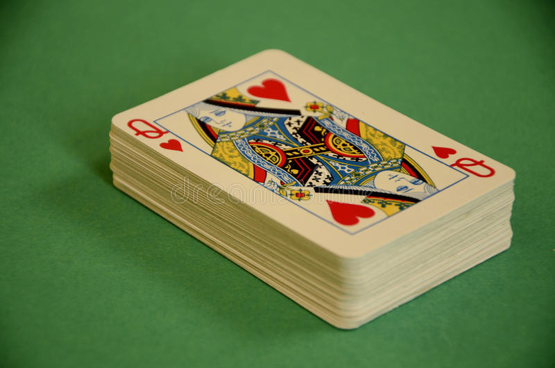 心脏的女王/王后在上面的纸牌甲板在绿色台面呢的 免版税库存图片
