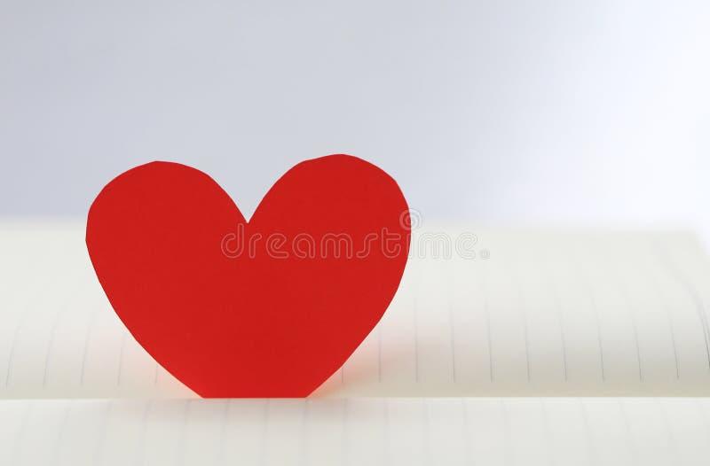 心脏红色纸在白皮书地板上塞住了 库存照片