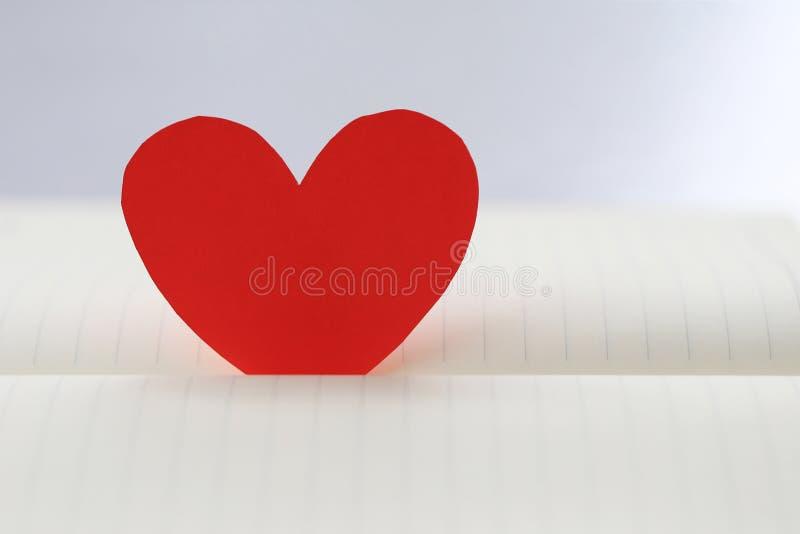 心脏红色纸在白皮书地板上塞住了 免版税库存照片
