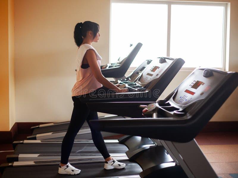 心脏锻炼 跑在踏车的适合妇女做在健身房的心脏训练,健康生活方式概念 免版税库存照片