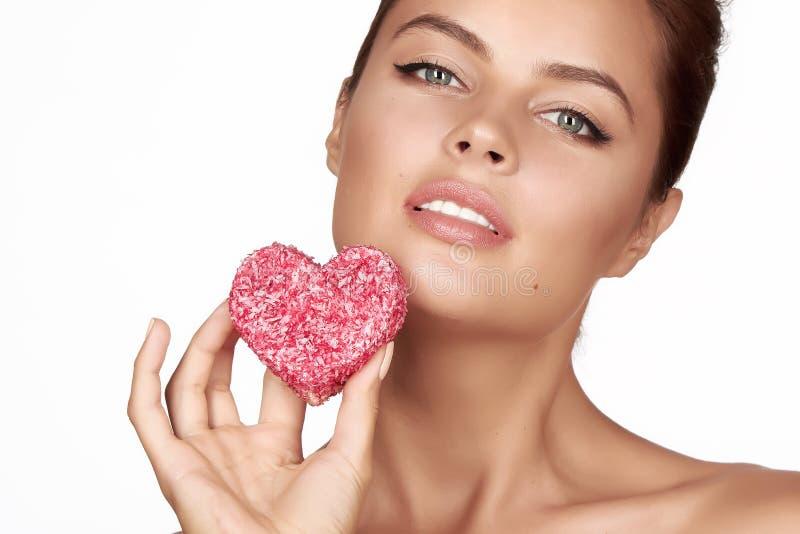 心脏,健康食物,鲜美,有机,浪漫华伦泰d美好的性感的深色的妇女吃蛋糕形状在白色背景的 库存照片