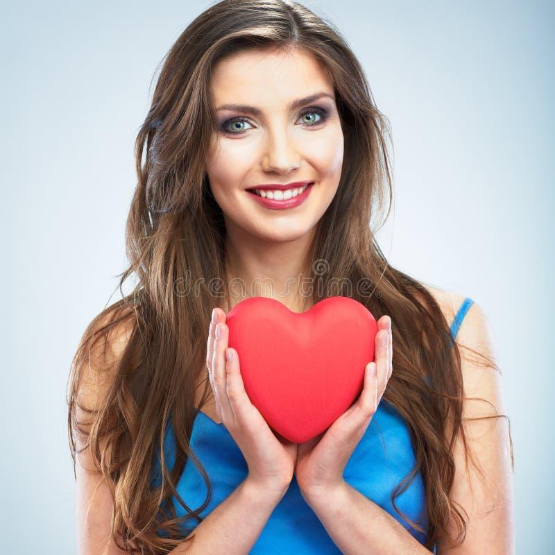 心脏,爱标志年轻愉快的妇女举行 隔绝在演播室b 免版税库存照片