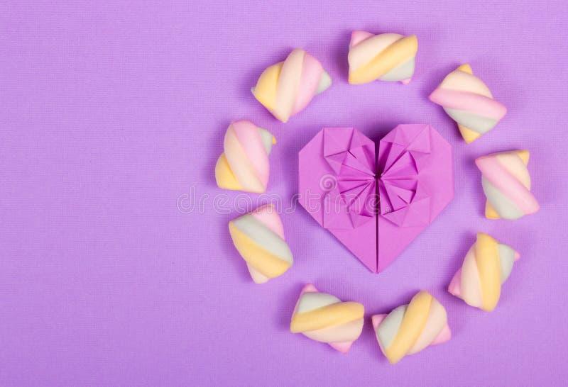 心脏origami和蛋白软糖在柔和的紫色背景 库存图片