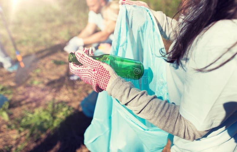 志愿与垃圾袋和瓶清洁区域 免版税库存照片