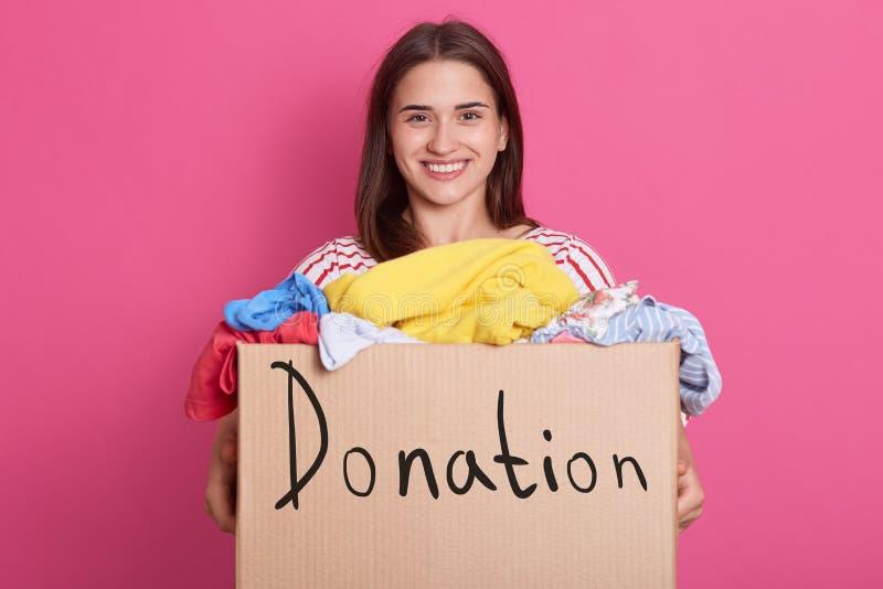志愿女性身分水平的射击被隔绝在桃红色背景在演播室,拿着有题字捐赠的箱子, 免版税库存照片