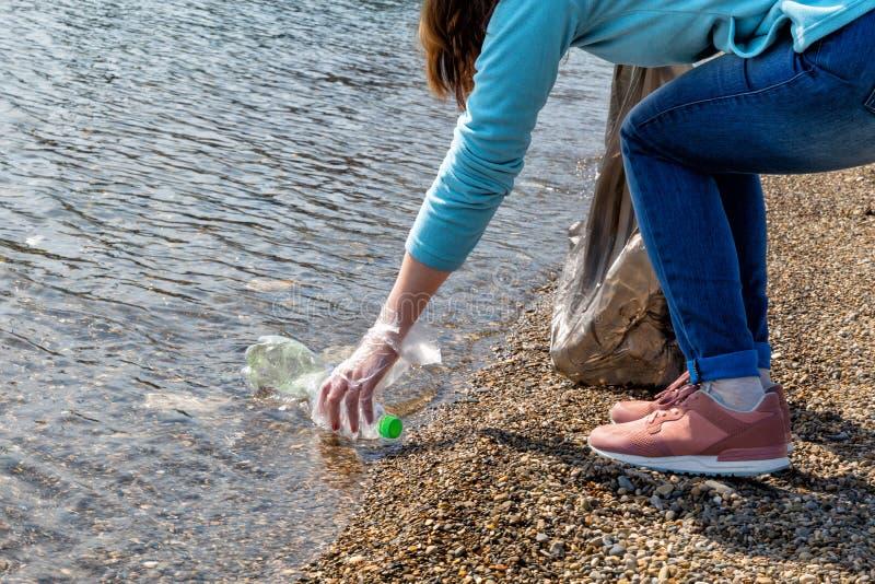志愿妇女从池塘收集垃圾 生态和环境洁净的保存的概念 免版税库存图片