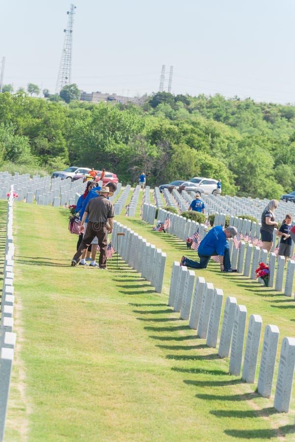 志愿者和家庭成员在下落的英雄头安置旗子 库存图片