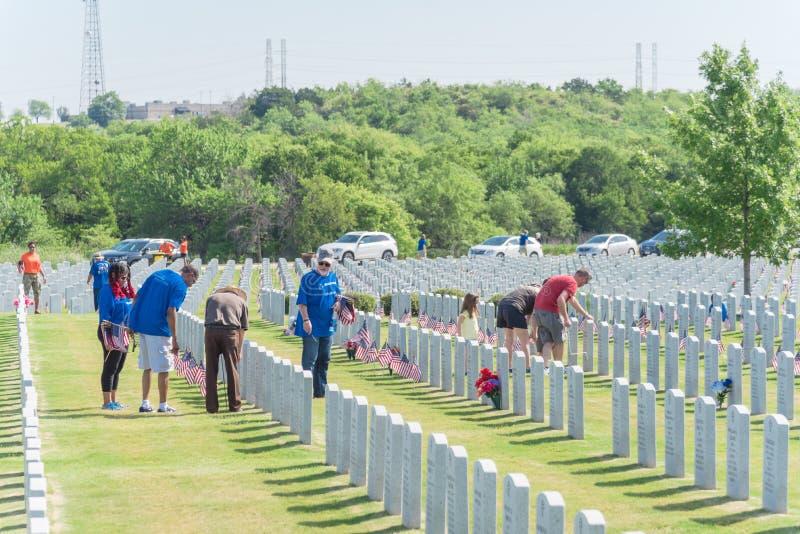 志愿者和家庭成员在下落的英雄头安置旗子 免版税库存图片