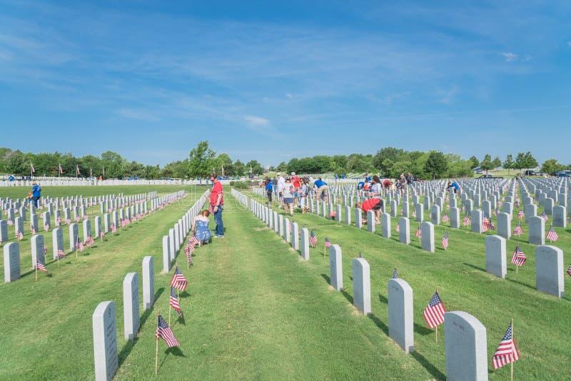志愿者和家庭成员在下落的英雄头安置旗子 图库摄影