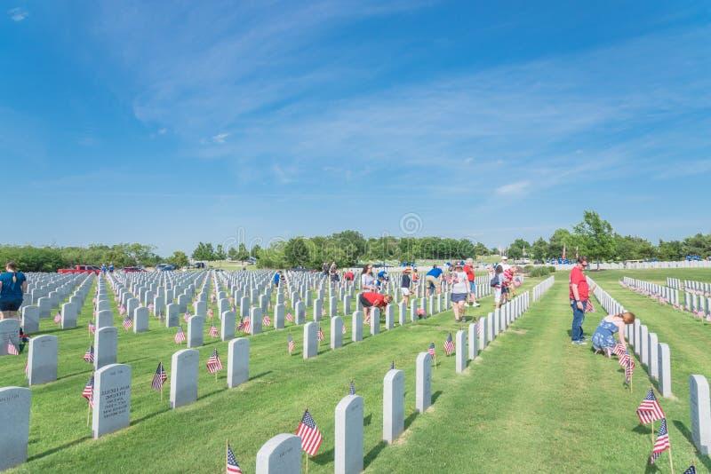 志愿者和家庭成员在下落的英雄头安置旗子 免版税库存照片