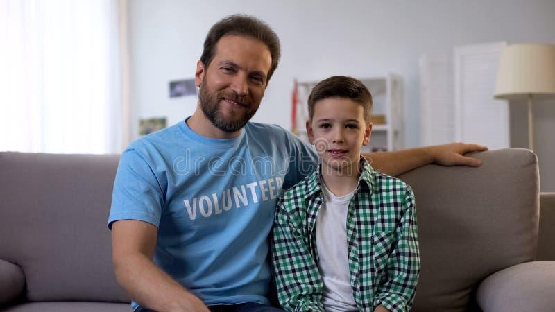 志愿者和男孩坐教练,全球性帮助的节目支持孤儿 免版税库存图片