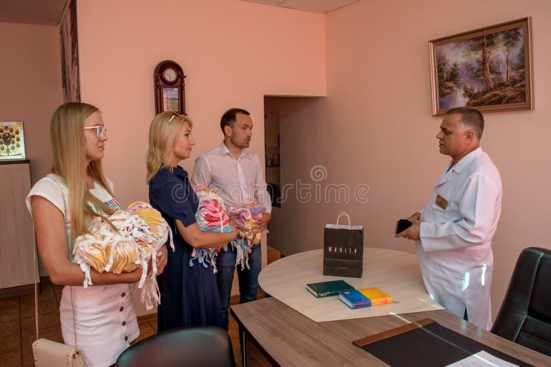 志愿者在产科医院合作捐赠婴孩的衣裳在儿童保护天期间 免版税库存照片