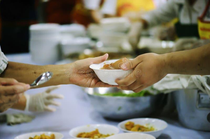 志愿者对解除饥饿的贫寒的份额食物:慈善概念 免版税库存照片