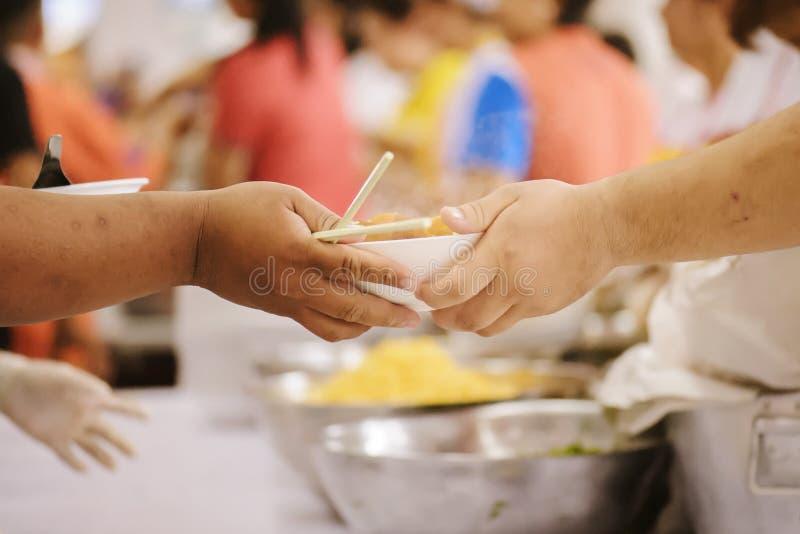 志愿者对解除饥饿的贫寒的份额食物:慈善概念 免版税库存图片