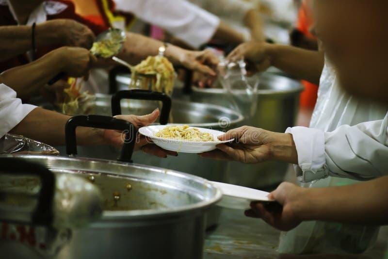 志愿者对解除饥饿的贫寒的份额食物:慈善概念 免版税图库摄影