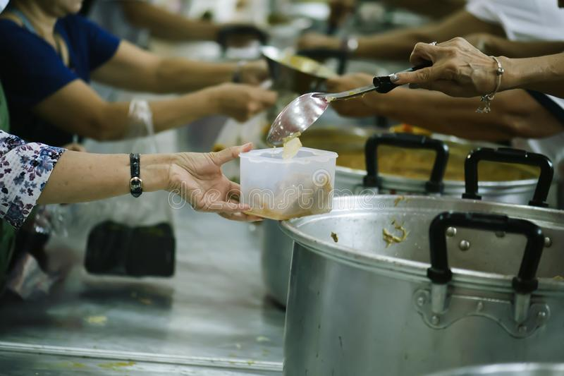 志愿者对解除饥饿的贫寒的份额食物:慈善概念 图库摄影