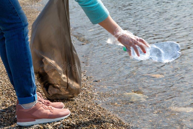 志愿者拉扯从海的塑料瓶 生态和环境洁净的保存的概念 图库摄影