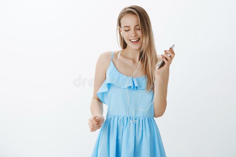 忘记所有麻烦的女孩作为享受听在应用程序的凉快的音乐通过智能手机,唱歌佩带的耳机和 免版税图库摄影