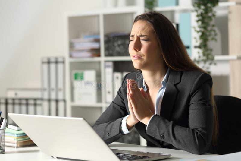 忧心忡忡的高管,晚上在办公室为笔记本电脑祈祷 免版税库存图片
