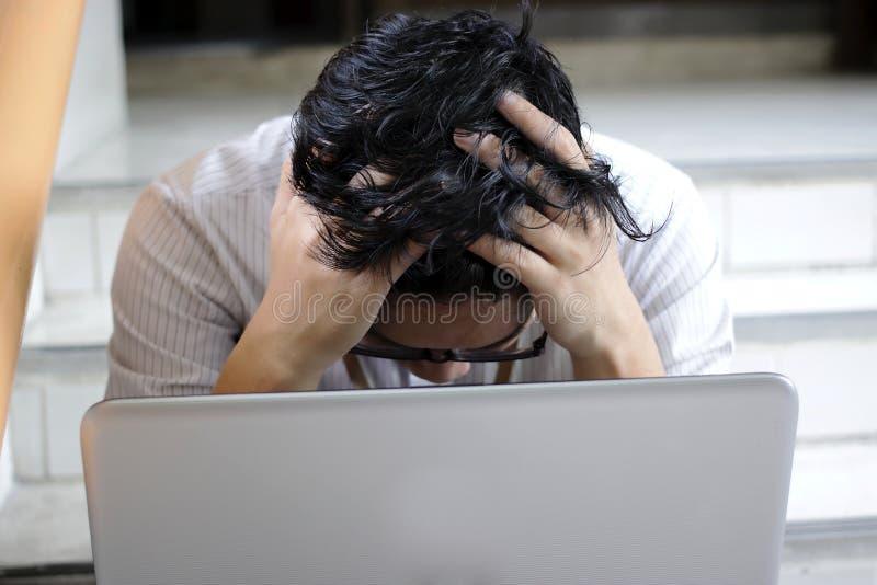 忧虑与年轻亚裔商人混淆膝上型计算机覆盖物面孔用他的手 库存照片