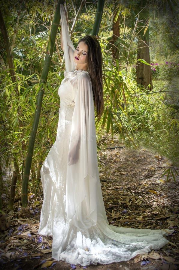 忧郁女孩在有哀伤的姿态的一个森林里 免版税库存照片