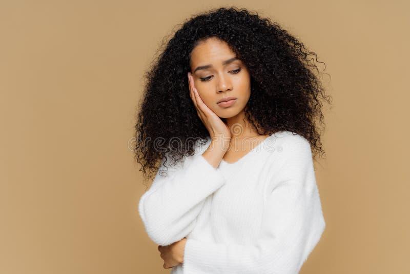 忧郁的哀伤的孤独的妇女聚焦下来与周道的表示,保留在面颊的手,有镇静表示,佩带白色 库存照片